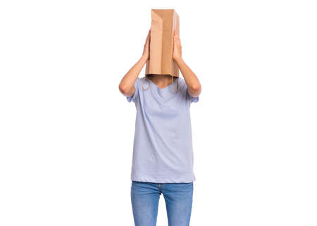 Portrait of teen girl with paper bag over her head covering ears with her hands, isolated on white background. Shy child pulling paper bag over her head closing ears with palms. Hear no evil concept.