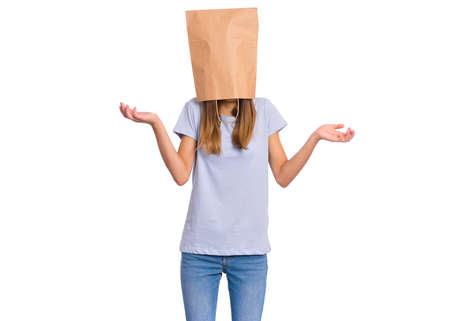 Teen girl with paper bag over her head showing helpless gesture with hands - I do not know, isolated on white background. Shrugging, shy child pulling paper bag over head making helpless sign.