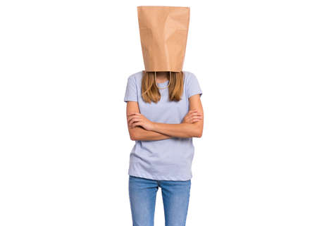 Portrait of teen girl with paper bag over head. Teenager cover head with bag with crossed arms isolated on white background. Child folded hands, pulling paper bag over head.