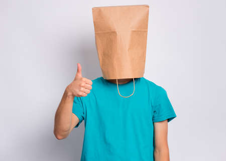 Portrait of teen boy with paper bag over head making thumb up gesture. Teenager cover head with bag showing success sign posing in studio. Child pulling paper bag over head. Stok Fotoğraf