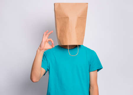 Portrait of teen boy with paper bag over head making Ok gesture. Teenager cover head with bag showing okay sign posing in studio. Child pulling paper bag over head. Stock fotó