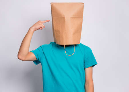 Portrait of teen boy show finger paper bag over head, isolated on white background. Child pointing finger at head with bag posing in studio. Teenager pulling paper shopping bag over head.