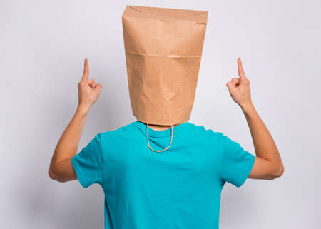 Portrait of teen boy - back view, with paper bag over head pointing hands up at copyspace, on gray background. Child pointing fingers at something - rear view. Stock fotó