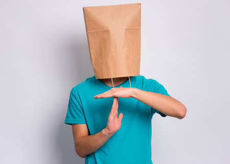 Portrait of teen boy with paper bag over head making timeout gesture on gray background. Child showing pause or time out sign.