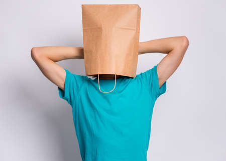 Portrait of teen boy, with paper bag over head taking rest, on gray background. Time to relax. Child holding hands behind his head having time-out. Stock fotó