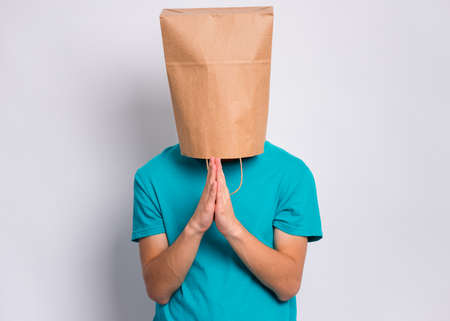 Portrait of teen boy praying, with paper bag over head, on gray background. Child with hands folded in prayer hoping for better. Teenager asking God for good luck, success or forgiveness.