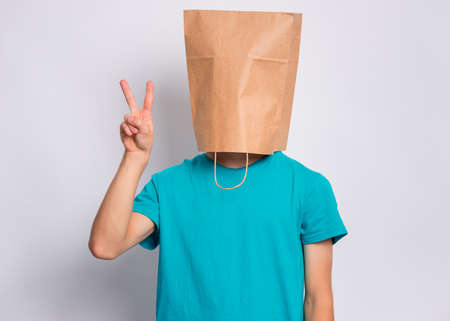 Portrait of teen boy with paper bag over head making Victory gesture. Teenager cover head with bag showing victory sign posing in studio. Child pulling paper bag over head. Stock fotó