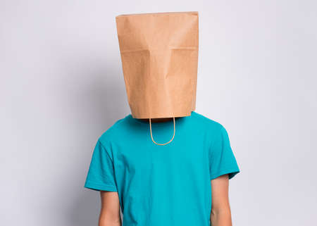 Portrait of teen boy with paper bag over head. Teenager cover head with bag posing in studio. Child pulling bag over head on gray background. Imagens