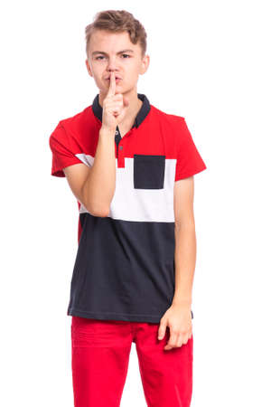 Teen boy asking to be quiet with finger on lips, isolated on white background. Cute young teenager making keep Quiet gesture. Child asking for silence or secrecy with finger on lips shh sign symbol. 免版税图像