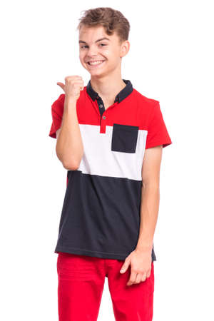 Portrait of teen boy pointing to back behind with hand and thumb up, isolated on white background. Cute young teenager smiling and attracted by attention pointing finger at something. Happy child.