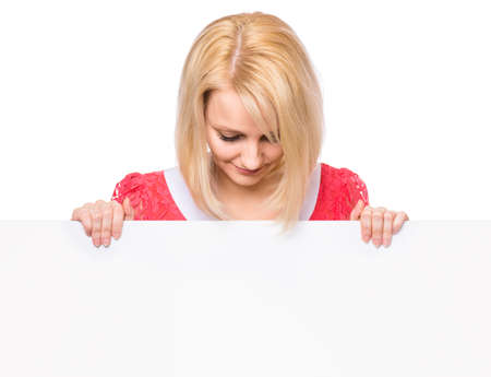 Portrait of happy smiling young woman, showing empty blank signboard with copyspace. Businesswoman holding big white banner, isolated on white background.