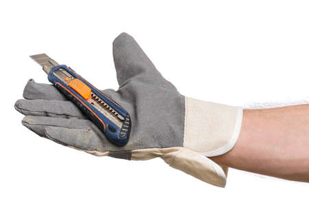Male Hand wearing Working Glove with Office knife. Human Hand holding Stationery Knife Cutter, Isolated on White Background. Banco de Imagens