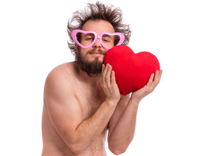 Happy Valentines Day. Crazy bearded Man with funny Haircut in eye Glasses. Happy and silly guy in Love, isolated on white background. Cheerful naked man with Red plush Heart. Фото со стока