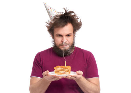 Crazy bearded Man with funny Haircut in birthday cap, isolated on white background. Guy holding plate with piece of birthday cake and burning candle. Holidays concept.