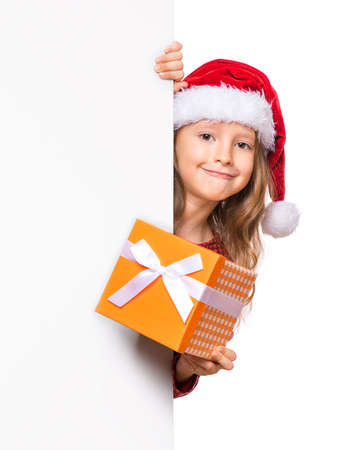 Beautiful Christmas little girl wearing red Santa hat holding banner sign. Smiling child showing white blank empty board for advertisement copyspace and gift box. Winter holidays. Happy New Year. Banco de Imagens