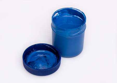 Opened blue Gouache jar, on white background with copy space. Cans of different colors gouache paints. Banco de Imagens