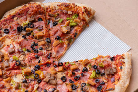 Delicious Italian pizza with bacon, olives, sausages and mushrooms. Top view. Fresh tasty pizza in cardboard box - close-up. Banco de Imagens