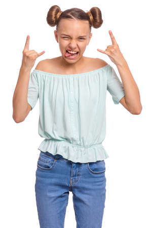 Funny teen girl making Rock Gesture, isolated on white background. Crazy teenager shows tongue and doing heavy metal rock sign. Problems of transitional age.