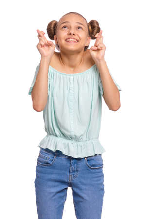 Portrait of teen girl crossing her fingers and wishing for good luck, isolated on white background. Caucasian teenager praying with crossed fingers, looking up. Child face expression emotions.
