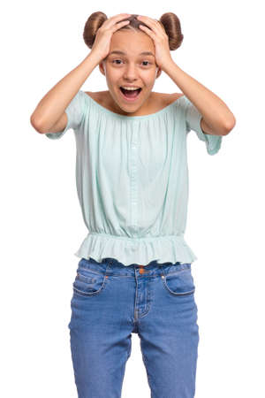 Portrait of surprised teen girl, isolated on white background. Funny child looking at camera in amazement, touching head with hands. Beautiful caucasian teenager, opening eyes and mouth with shock. Banco de Imagens