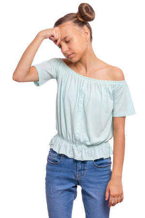 Portrait of tired teen girl touching head suffering headache. Sad teenager isolated on white background. Unhappy beautiful caucasian young teenager suffering from headache. Banco de Imagens