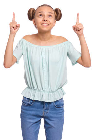 Portrait of teen girl pointing fingers up at copyspace, isolated on white background. Beautiful caucasian young teenager attracted by attention at something. Happy child looking up.