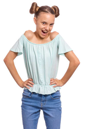 Portrait of happy teen girl with funny hairstyle, isolated on white background. Smiling child with hands on waist looking at camera. Beautiful young caucasian teenager.