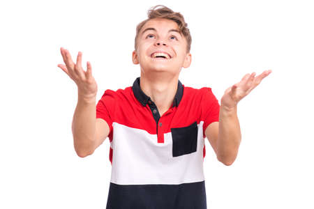 Portrait of teen boy raised hands and trying to catch something. Cute caucasian young teenager looking up, isolated on white background. Joyful child having fun.