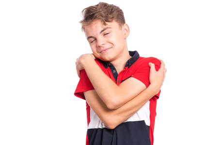 Self love and self care. Portrait of teen boy Hugging oneself, isolated on white background. Happy funny child. Cute caucasian young teenager smiling with eyes closed. Banco de Imagens