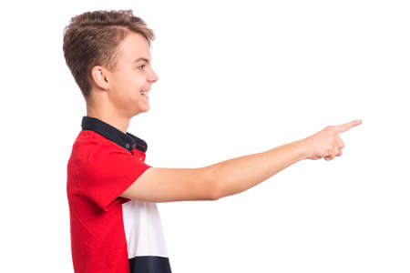 Portrait of teen boy pointing finger away at copyspace - side view, isolated on white background. Happy teenager smiling and pointing fingers at something. Cute child looking away - profile. Banco de Imagens