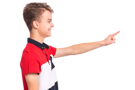 Portrait of teen boy pointing finger away at copyspace - side view, isolated on white background. Cute teenager smiling and pointing fingers at something. Happy child looking away - profile.