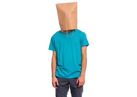 Portrait of teen boy with paper bag over head. Modest Teenager cover head with bag posing in studio. Shy Child pulling bag over head isolated on white background.