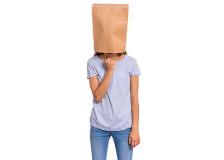 Portrait of teen girl with paper bag over head. Teenager cover head with bag holding hand near face isolated on white background. Child pulling paper bag over head.