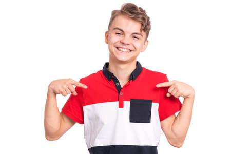 Portrait of handsome teen boy pointing oneself, isolated on white background. Happy smiling child looking at camera. Emotions and signs concept. Young student points fingers at himself Banco de Imagens