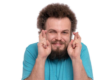 Portrait of bearded man with funny curly hair crossing his fingers and wishing for good luck. Happy crazy male smiling, isolated on white background.