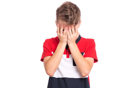Portrait of teen boy with sad expression covering face with hands while crying. Upset caucasian young teenager, isolated on white background. Unhappy child crying, not showing his tears.