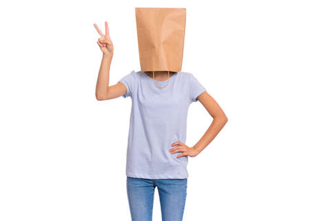 Portrait of teen girl with paper bag over head making Victory gesture. Teenager showing victory sign isolated on white background. Happy child posing in studio. Banco de Imagens