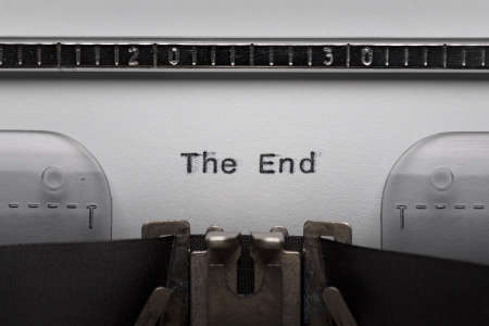 Typing text THE END on vintage manual typewriter. Close up of writes words on white paper. Shot in macro. Stock Photo