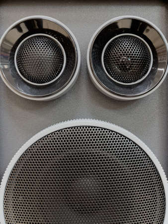 Close-up of musical stereo speaker with protective grill. Modern grey and black audio speaker or music column for background.