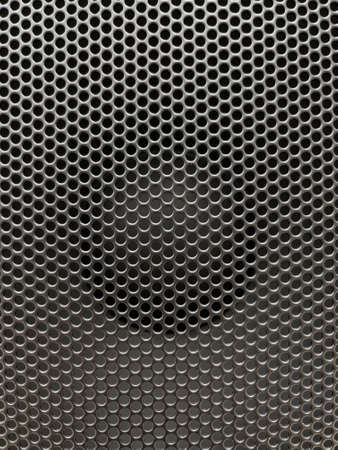Close-up of musical stereo speaker with protective grill. Modern black audio speaker or music column for background.