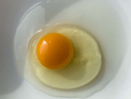 One bright yellow raw chicken egg in a white bowl.