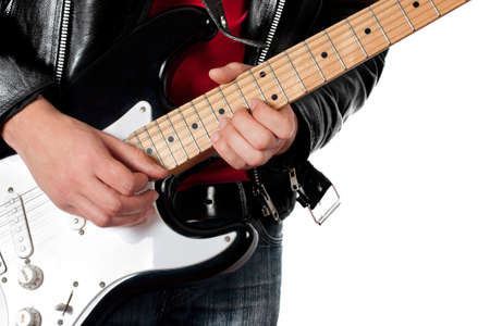 Young guy in leather jacket playing electric guitar on white photo