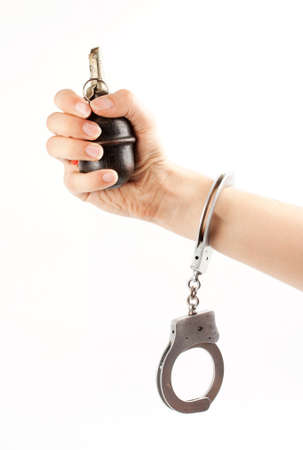Hand holding a grenade in handcuffs isolated on white Stock Photo - 12699513