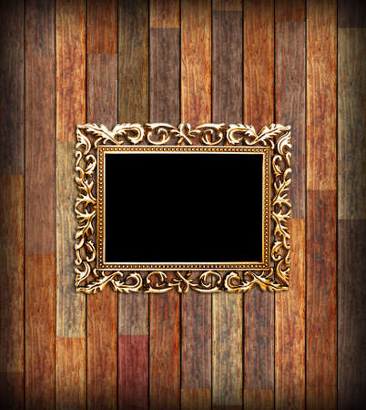 black metallic background: Empty golden frame, on a wood wall