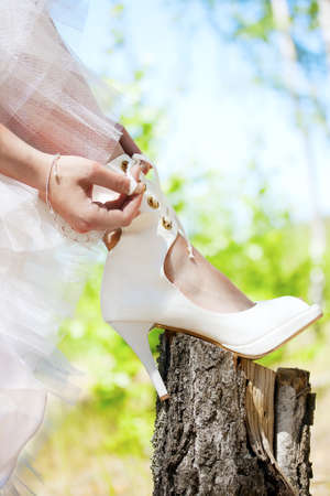 bride lacing white shoes