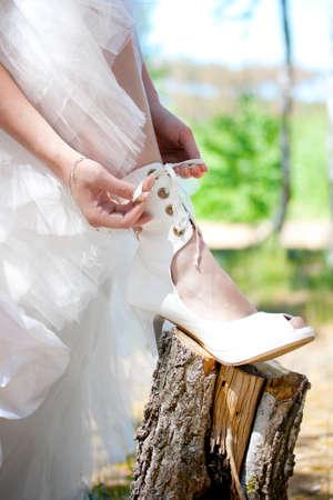 bride lacing white shoes photo