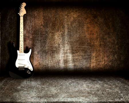 la guitarra en la habitación de acero sobre un fondo grunge