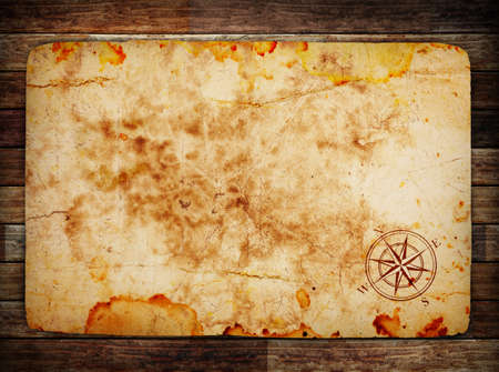 unknown age: old treasure map on wooden background wih compass