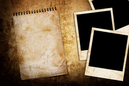 infamous: old used notebook on grunge background with photo frame