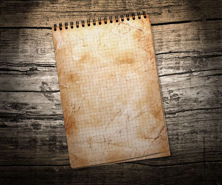 infamous: old used notebook on wood background